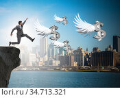 Businessman chasing angel dollars in business concept. Стоковое фото, фотограф Elnur / Фотобанк Лори