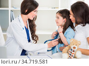 Young smiling female pediatrician doctor and her little patient with... Стоковое фото, фотограф Zoonar.com/Ivan Mikhaylov / easy Fotostock / Фотобанк Лори