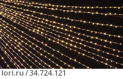 Garland with cross beams burn and flicker in soft defocused bokeh. Flickering garlands for Christmas or New Year background. Beautiful Christmas background of warm golden lights. 4K. Стоковое видео, видеограф Dmitry Domashenko / Фотобанк Лори