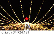 Christmas tree with red star in bokeh effect on dark background outdoors. Silhouette Christmas tree with many flickering garlands in bright bokeh. Merry Christmas and Happy New Year concept. 4K. Стоковое видео, видеограф Dmitry Domashenko / Фотобанк Лори