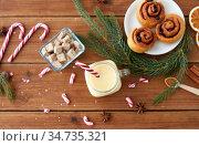 eggnog with candy cane in mug and cinnamon buns. Стоковое фото, фотограф Syda Productions / Фотобанк Лори