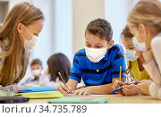 group of students in masks learning at school. Стоковое фото, фотограф Syda Productions / Фотобанк Лори