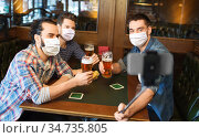 men in masks take selfie and drink beer at bar. Стоковое фото, фотограф Syda Productions / Фотобанк Лори