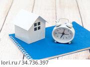 Часы и домик на синем блокноте. Планирование покупки жилья в кредит. Стоковое фото, фотограф Наталья Осипова / Фотобанк Лори