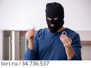 Male robber stealing valuable things from the house. Стоковое фото, фотограф Elnur / Фотобанк Лори