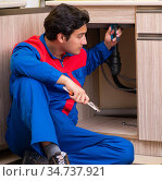 Plumber repairing wash basin at kitchen. Стоковое фото, фотограф Elnur / Фотобанк Лори