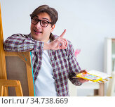 Young male artist drawing pictures in studio. Стоковое фото, фотограф Elnur / Фотобанк Лори