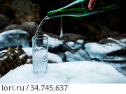 Mineral mineral water is poured from a glass green bottle into a clear... Стоковое фото, фотограф Zoonar.com/Ian Iankovskii / easy Fotostock / Фотобанк Лори