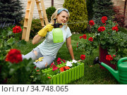 Woman with spray watering flowers in the garden. Стоковое фото, фотограф Tryapitsyn Sergiy / Фотобанк Лори