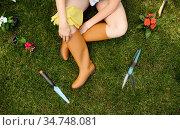 Female gardener sitting on the grass in the garden. Стоковое фото, фотограф Tryapitsyn Sergiy / Фотобанк Лори
