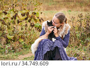 Young woman dressed in ethnic style with a kitten in her arms crouched against the background of a blurred autumn landscape (2020 год). Редакционное фото, фотограф Евгений Харитонов / Фотобанк Лори