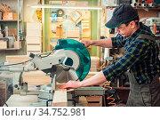 Carpenter worker cutting wooden board with circular saw. Profession... Стоковое фото, фотограф Zoonar.com/Ruslan Olinchuk / easy Fotostock / Фотобанк Лори