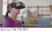 Woman using VR headset while performing yoga at home. Стоковое видео, агентство Wavebreak Media / Фотобанк Лори