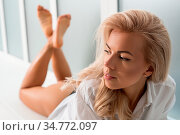 Young blonde with long locks in underwear lying on her stomach on... Стоковое фото, фотограф Zoonar.com/Andrey Guryanov / easy Fotostock / Фотобанк Лори