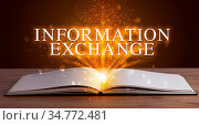 INFORMATION EXCHANGE inscription coming out from an open book, educational... Стоковое фото, фотограф Zoonar.com/ranczandras / easy Fotostock / Фотобанк Лори