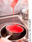 Cooking mirror glaze, red liquid in the pan. Стоковое фото, фотограф Zoonar.com/Oksana Shufrych / easy Fotostock / Фотобанк Лори