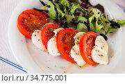 Fresh italian caprese salad with mozzarella and tomatoes on white plate. Стоковое фото, фотограф Яков Филимонов / Фотобанк Лори