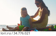 mother and daughter playing with toys on beach. Стоковое видео, видеограф Syda Productions / Фотобанк Лори