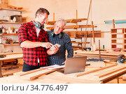 Handwerker lesen zusammen eine SMS auf dem Smartphone in der Werkstatt. Стоковое фото, фотограф Zoonar.com/Robert Kneschke / age Fotostock / Фотобанк Лори