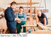 Handwerker Team mit Azubi arbeitet zusammen in der Werkstatt mit ... Стоковое фото, фотограф Zoonar.com/Robert Kneschke / age Fotostock / Фотобанк Лори