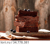Stack of square baked slices of brownie chocolate cake with walnuts... Стоковое фото, фотограф Zoonar.com/Danko Natalya / easy Fotostock / Фотобанк Лори