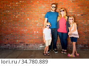 Young Caucasian Family Wearing Sunglasses Against Brick Wall. Стоковое фото, фотограф Zoonar.com/Andy Dean Photography / easy Fotostock / Фотобанк Лори