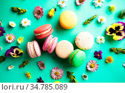 Appetizing colorful macaroons and beautiful flowers on green background... Стоковое фото, фотограф Zoonar.com/Oksana Shufrych / easy Fotostock / Фотобанк Лори