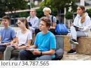 Teenagers preparing schoolwork outside school. Стоковое фото, фотограф Яков Филимонов / Фотобанк Лори