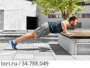 young man doing push ups on city street. Стоковое фото, фотограф Syda Productions / Фотобанк Лори