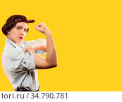 Strong woman show her biceps on yellow background with copy space. Стоковое фото, фотограф Zoonar.com/A.Tugolukov / easy Fotostock / Фотобанк Лори