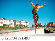 A teenager skateboarder does an ollie trick in a skatepark on the... Стоковое фото, фотограф Zoonar.com/Ian Iankovskii / easy Fotostock / Фотобанк Лори