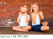 Cute Young Cuacasian Boy and Girl Eating Watermelon Against Brick... Стоковое фото, фотограф Zoonar.com/Andy Dean Photography / easy Fotostock / Фотобанк Лори