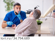 Old patient visiting young male doctor in blood transfusion conc. Стоковое фото, фотограф Elnur / Фотобанк Лори