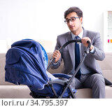 Businessman looking after newborn baby at home and teleworking. Стоковое фото, фотограф Elnur / Фотобанк Лори