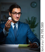 Young employee with golf ball in office. Стоковое фото, фотограф Elnur / Фотобанк Лори