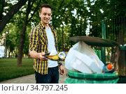 Young volunteer puts trash in plastic bin in park. Стоковое фото, фотограф Tryapitsyn Sergiy / Фотобанк Лори