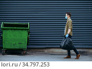 Volunteer carries plastic trash bags to the can. Стоковое фото, фотограф Tryapitsyn Sergiy / Фотобанк Лори