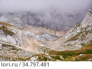 Rocky alpine gorge with melting glacier partially obscured by a cloud. Стоковое фото, фотограф Евгений Харитонов / Фотобанк Лори