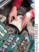Male repairman hands inserting air filter cartridge in plastic box of car engine, tools kit is on a foreground. Стоковое фото, фотограф Кекяляйнен Андрей / Фотобанк Лори