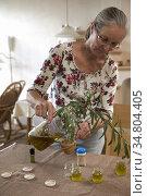Maria confectionnant un baume aux plantes sauvages, ferme auberge... Редакционное фото, фотограф Christian Goupi / age Fotostock / Фотобанк Лори