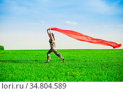 Beautiful young woman jumping on a green meadow with a colored red... Стоковое фото, фотограф Zoonar.com/Aleksandr Markin / easy Fotostock / Фотобанк Лори