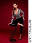 Pretty brunette in sexy shirt near bar stool portrait against burgundy... Стоковое фото, фотограф Zoonar.com/Andrey Guryanov / easy Fotostock / Фотобанк Лори