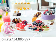Many sweet pastries on white table with fresh summer berries. Festive... Стоковое фото, фотограф Zoonar.com/Viktoria Kondysenko / easy Fotostock / Фотобанк Лори