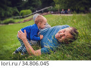 Father and son rolling downhill on the grass in a park in spring. Стоковое фото, фотограф Zoonar.com/Pawel Opaska / easy Fotostock / Фотобанк Лори