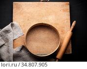 Vintage wooden rolling pin and a round sieve, gray linen napkin, black... Стоковое фото, фотограф Zoonar.com/Danko Natalya / easy Fotostock / Фотобанк Лори