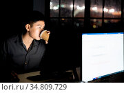 Young adult asian businessman drinking hot cofee while working late... Стоковое фото, фотограф Zoonar.com/Vichie81 / easy Fotostock / Фотобанк Лори