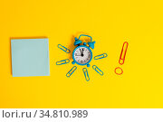 Metal alarm clock wakeup clips rubber band notepad colored background. Стоковое фото, фотограф Zoonar.com/Artur Szczybylo / easy Fotostock / Фотобанк Лори