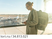 Casually dressed female traveler at airport looking at smart phone... Стоковое фото, фотограф Zoonar.com/Matej Kastelic / easy Fotostock / Фотобанк Лори