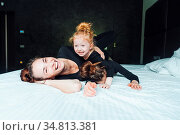 Mom and two daughters have fun on the bed in the bedroom. Стоковое фото, фотограф Zoonar.com/Oleksii Hrecheniuk / easy Fotostock / Фотобанк Лори