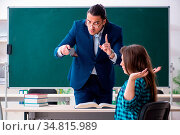Young handsome teacher and female student in the classroom. Стоковое фото, фотограф Zoonar.com/Elnur Amikishiyev / easy Fotostock / Фотобанк Лори